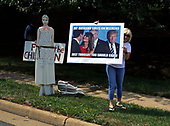 Protesters display signs outside Trump National Golf Club in Sterling, Virginia during the president's 3 1/2 visit to the club on Labor Day, September 2, 2019.<br /> Credit: Martin H. Simon / Pool via CNP