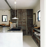 A contemporary kitchen where natural, salvaged materials are blended with ultra-modern concrete for an exciting mix of old and new. A pendant light hangs above a sink set in a large island unit.