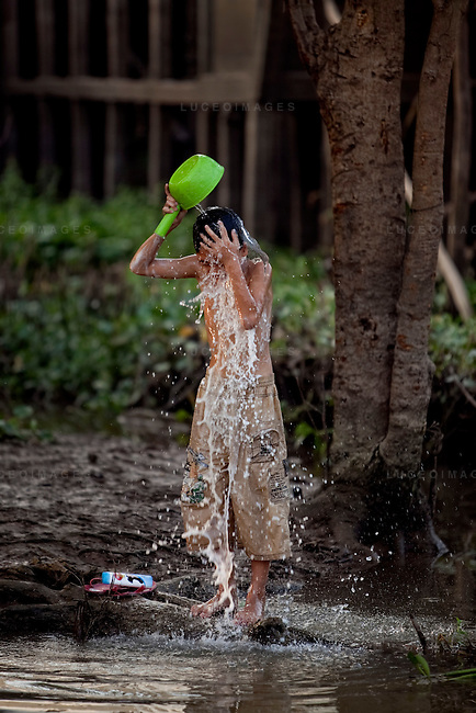 """Son, 12, bathes himself in the Hau Giang River, a tributary of the Mekong River, in Chau Doc, in the An Giang Province, Vietnam. When the Mekong River reaches Vietnam it splits into two smaller riveres. The """"Tien Giang"""", which means """"upper river"""" and the """"Hau Giang"""", which means """"lower river"""". Photo taken on Monday, December 7, 2009. Kevin German / Luceo Images"""