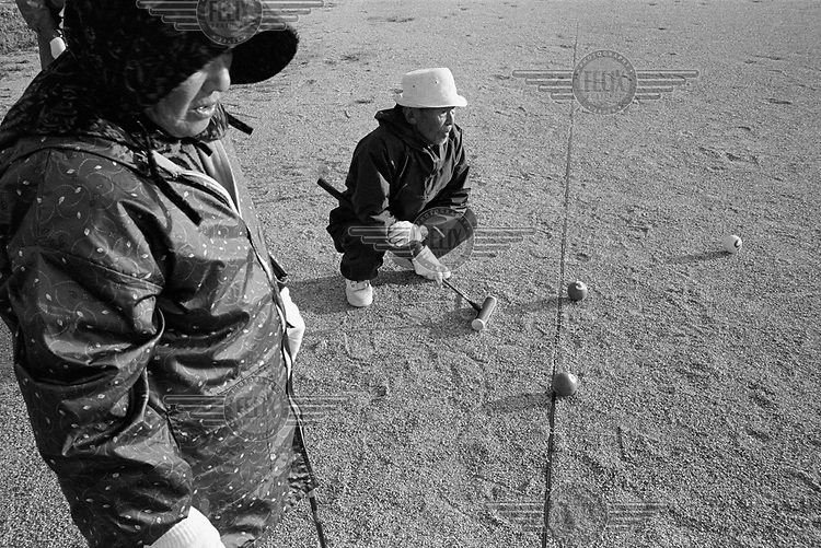 Elderly people playing gateball (a version of croquet).