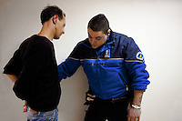 "Switzerland. Geneva. BSR (Brigade de sécurité routière) police station. A police officer and a handcuffed french man, who was arrested because he was driving under the influence of alcohol. He is bleeding blood from his right ear. Driving under the influence (DUI), drunken driving, drunk driving, drink driving, operating under the influence, drinking and driving, or impaired driving is the act of driving a motor vehicle with blood levels of alcohol in excess of a legal limit (""Blood Alcohol Content"", or ""BAC""). A police station or station house is a building which serves police officers and contains offices, temporary holding cells and interview/interrogation rooms. The BSR police station is located in the Grand-Lancy area. 01.04.12 © 2012 Didier Ruef"