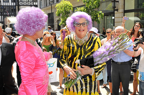 Dame Edna Everage (John Barry Humphries) attending the photocall for 'Eat Pray Laugh' farewell tour, London Palladium, London, England. <br /> 15th July 2013<br /> half length black white dress wig glasses pink   flowers bouquet fan<br /> CAP/MAR<br /> &copy; Martin Harris/Capital Pictures