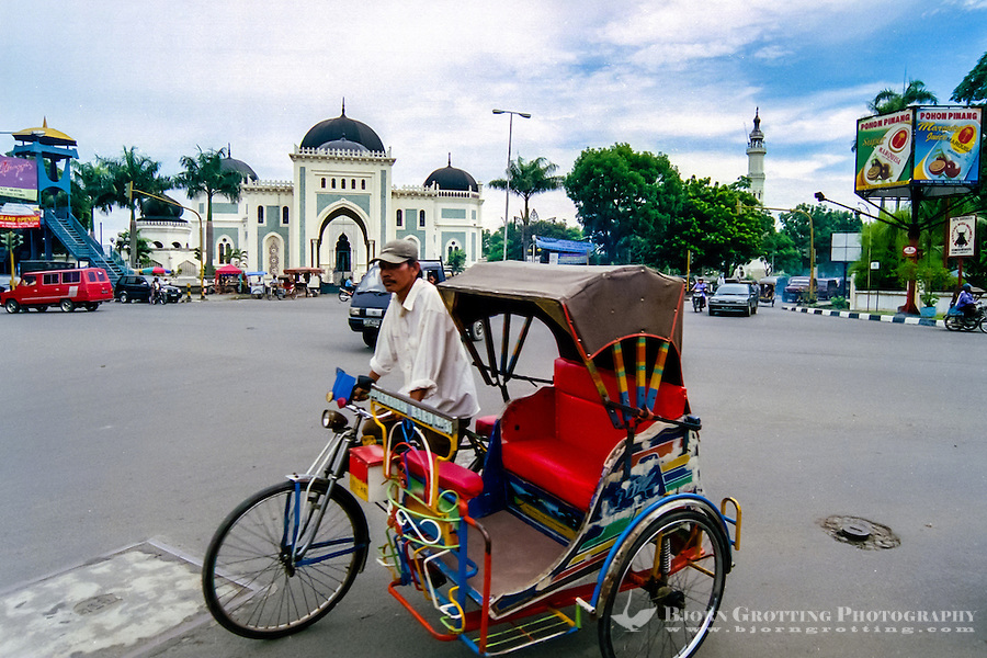 Indonesia, Sumatra. Medan. A colourful becak in front of Mesjid Raya.