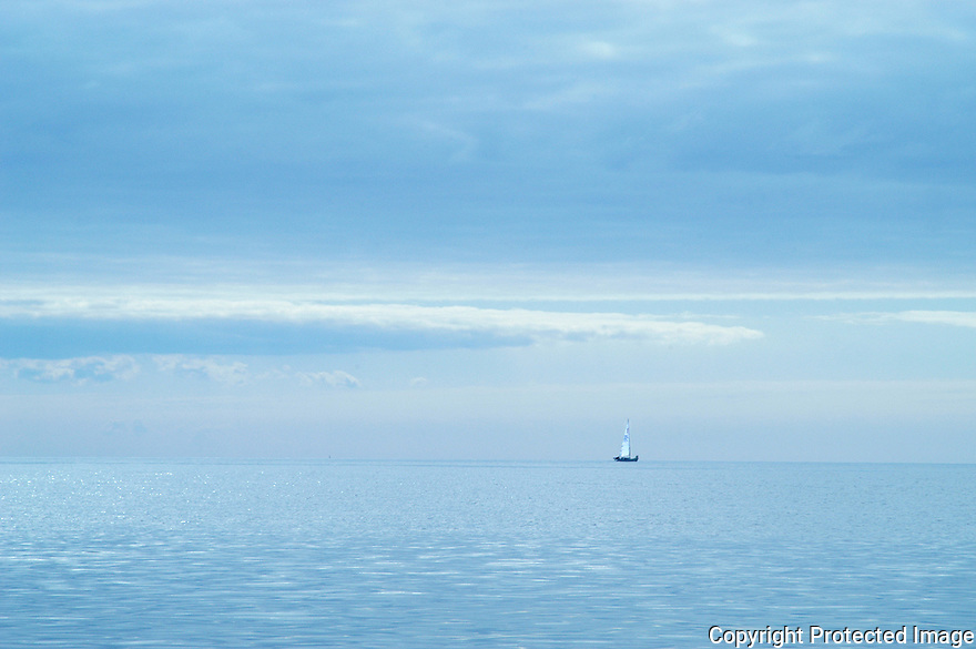 A singel sailboat in the open blue ocean