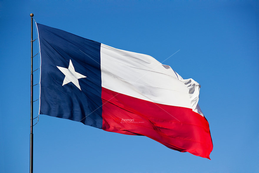 A Texas flag stands out against a cloudless blue sky as it flys in a steady wind in Austin, Texas.