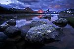 A single shaft of sunlight breaks the cloud cover and illuminates a peak, Jasper National Park, Alberta, Canada