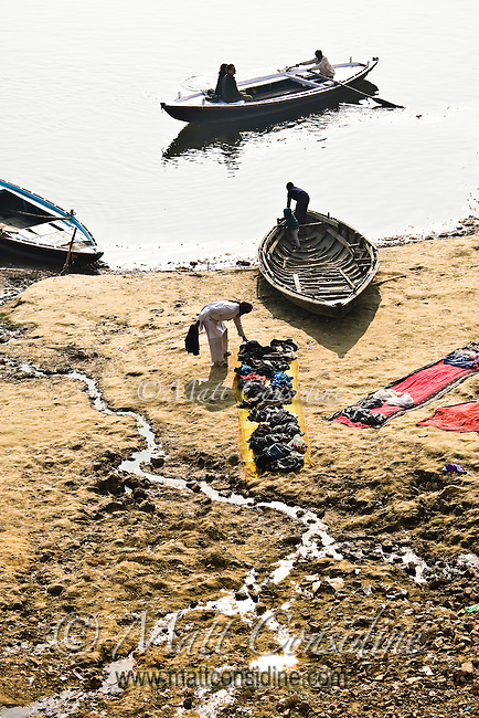 Scene of boatman with pilgrims heading for river trip while laundryman is drying clothes on the bank of river Ganga in Varanasi.<br /> (Photo by Matt Considine - Images of Asia Collection)