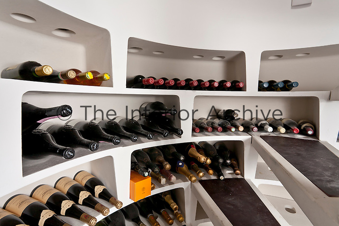 Circular bins filled with wine bottles line the treads of a spiral staircase in a wine cellar concealed beneath the floor of the living room