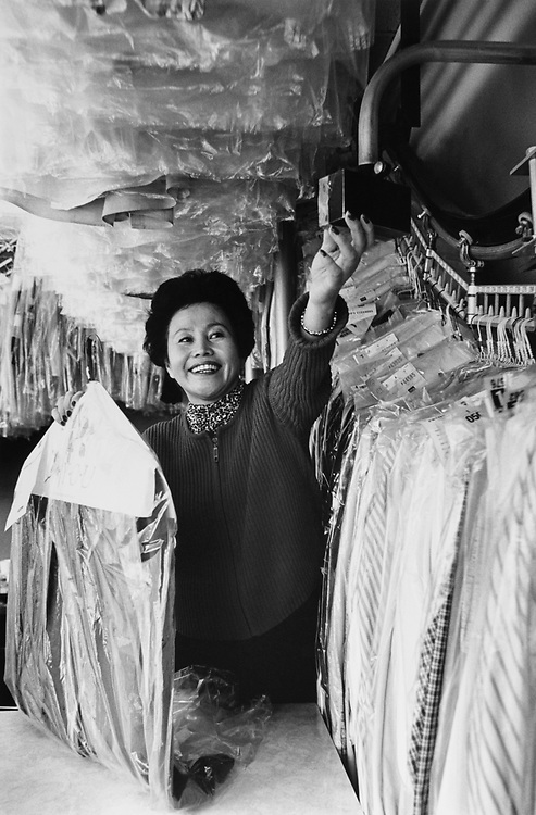 Amy Kwon holding clothes in Frenchie's Cleaners, 237 Pennsylvania Ave SE, employee, on Nov. 18, 1996. (Photo by CQ Roll Call via Getty Images)