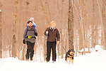 A father carries his baby on his backpack while cross-country skiing with his wife and dog.   Watson's Wonder Trail, Smugglers' Notch, Vermont.