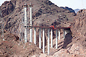 Colorado River Bridge construction. Traffic currently travels on a two lane road over Hoover Dam which causes traffic congested and poses a security risk. Large trucks are not allowed over the dam and must make a major detour around the area. To deal with these problems the US 93 Highway, Hoover Dam Bypass project was developed approximately 1,500 feet downstream of the dam. It consists of 3.5 miles of roadway, two lanes in each direction, with a 1,900 foot long twin-rib concrete arch bridge 880 feet above the Colorado River's Black Canyon. It will be the longest concrete arch in the US and the 5th longest in the world. It will involve 60,000 cubic yards of concrete, 8,000 tons of steel, over 3.5 million cubic yards of earthwork excavation/embankment, and cost approximately $240 million.* Construction began in 2005 and is expected to be completed in 2010. US 93 is on the North American Free Trade Agreement (NAFTA) route between Mexico and Canada, and it is also the major commercial route between the states of Arizona, Nevada, and Utah. Photo taken February 2009..*Statistics source: Central Federal Lands Highway Division of the U.S. Department of Transportation's Federal Highway Administration, the lead managers of the project.