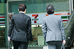 People walk past a Seven & iHoldings Co. signboard on display outside its headquarters building on April 11, 2016, Tokyo, Japan. Toshifumi Suzuki, Seven iHoldings Co. chairman and CEO abruptly announced his resignation at a news conference on Thursday after the company board rejected his proposal to replace Ryuichi Isaka, president of 7-Eleven Japan. Isaka was considered to be a potential future successor to Suzuki at the head of the retail group and it was rumored that Suzuki was trying remove Isaka in order to pave the way for his son to take over in the future. (Photo by Rodrigo Reyes Marin/AFLO)