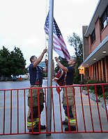 NWA Democrat-Gazette/ANDY SHUPE<br /> Edward Maria (left), and Marcus Mason, both firefighters with the Fayetteville Fire Department, work together Friday, Sept. 11, 2015, to raise the U.S. and Arkansas flags to half staff outside the department's Station One in Fayetteville. The U.S. flag that bears the names of victims of the Sept. 11, 2001 terrorist attacks and was flown at half staff on the 14th anniversary of the attacks.