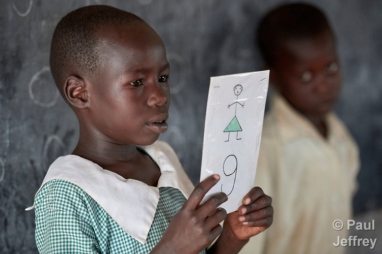 "A girl holds a sign for the letter ""G"" during a class in the Catholic Church-sponsored St. Daniel Comboni Primary School in Lugi, a village in the Nuba Mountains of Sudan. The area is controlled by the Sudan People's Liberation Movement-North, and frequently attacked by the military of Sudan. The church has sponsored schools and health care facilities throughout the war-torn region."