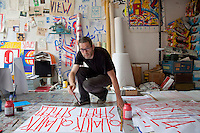 "SP38, a French artist in his studio in East Berlin painting placards with the slogan ""Quality Street"". He posts the placards on the sides of buildings as an ironic comment on the gentrification of former run-down districts of East Berlin that attracted many international artists after the fall of the Berlin Wall due to their affordable rents (or often free rents in numerous abandoned building which were squatted). Areas in East Berlin popular with artists are now becoming more expensive as trendy restaurants and galleries have followed in the artists' wake."