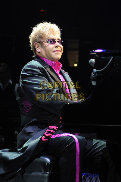 SIR ELTON JOHN.performs at Copps Coliseum during his Rocket Man Greatest Hits Tour, Hamilton, Ontario, Canada,.10th July 2010..music concert gig live on stage half length pink shirt sunglasses playing tongue sticking out funny  at piano glasses microphone side kiss word scarf suit writing words .CAP/ADM/BPC.©Brent Perniac/AdMedia/Capital Pictures.