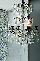 The chandelier in the bathroom was found in a market. The glow from the candles reflected in the crystal drops adds a touch of warm colour to the cool grey shades of the room