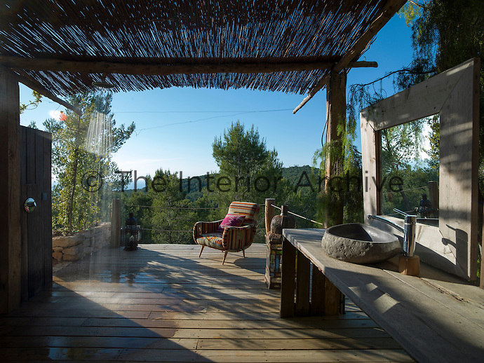 A shower rose attached to the bamboo roof of the covered terrace creates an impromptu outdoor shower room