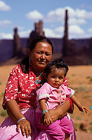 Indian mother with baby and The Totem Poles rock pillars in Monument Valley National Park and navaho Indian reservation,  Utah, USA