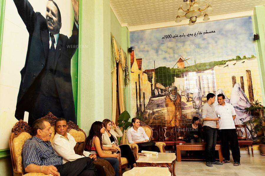 Algerie. Mascara. 15  Avril 2011.L'ecrivain Yasmina Khadra assis  sous le portrait geant du president Abd El Aziz Bouteflika dans le cadre d'une conference qu il donnait, organisee par l'association culturelle de la ville.<br /> <br /> <br /> Algeria, Mascara. April 15th 2011. The writer Yasmina Khadra sitting under the giant photo of president Abd El Aziz Bouteflika as part of a conference he was giving, organized by the cultural association of the city.