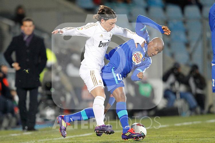 Getafe's Tshepo Masilela and Real Madrid's Mesut Ozil  during la Liga match on February 4th 2012. ..Photo: Cesar Cebolla / ALFAQUI