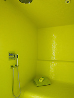 The shower room is lined in acid yellow mosaic tiles