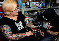 Tattoo artist, Cory Kapczynski, draws draft artwork for Shelly Schmidt at Capitol City Tattoo on Monday, December 8, 2014 in Madison, Wisconsin