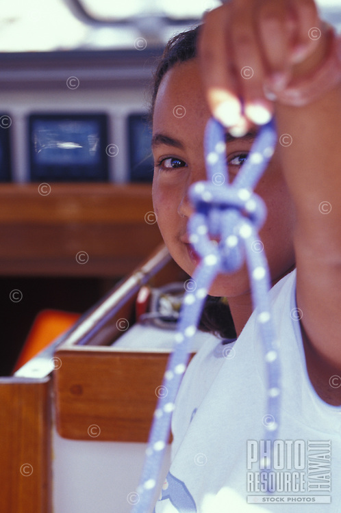 Young girl proudly displays her bowline knot tying prowess aboard sailing vessel 'Heron'