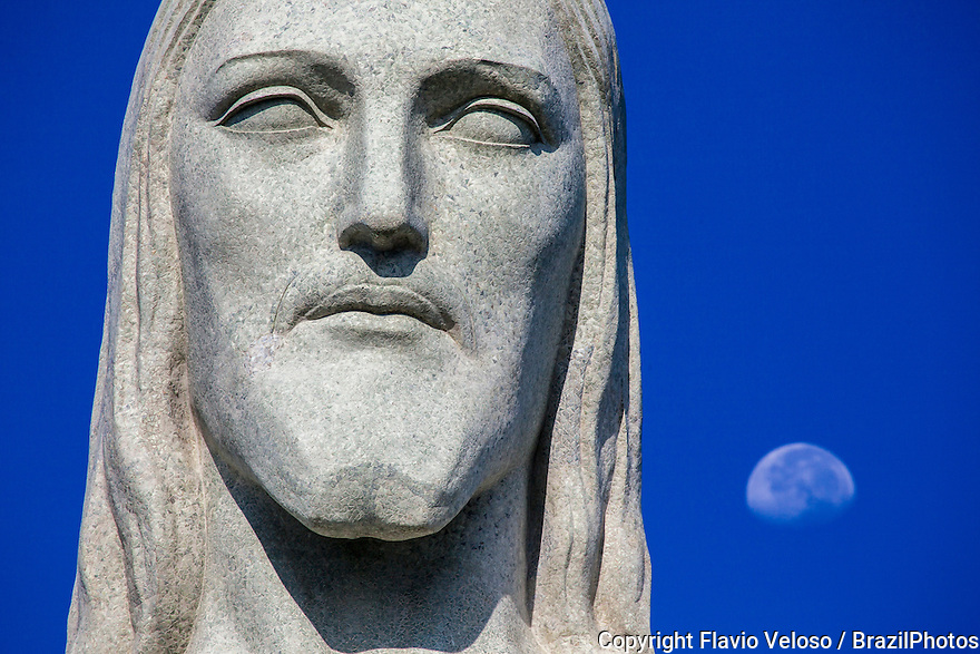 Christ the Redeemer statue face detail with moon in background. In Portuguese Cristo Redentor is a statue of Jesus Christ in Rio de Janeiro, Brazil and is located at Corcovado mountain in the Tijuca Forest National Park overlooking the city. Named one of the New Seven Wonders of the World in a list compiled by the Swiss-based The New Open World Corporation.