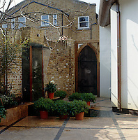 A modern water feature is the focal point of this brick-walled garden which is overlooked by neighbouring Georgian homes