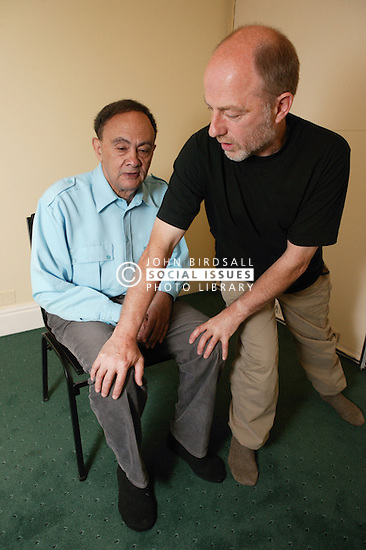 Teacher performing Alexander technique semisupine with patient in treatment room,
