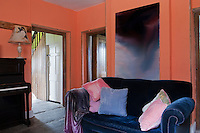 The second living room is painted orange which contrasts with the deep blue of the velvet sofa