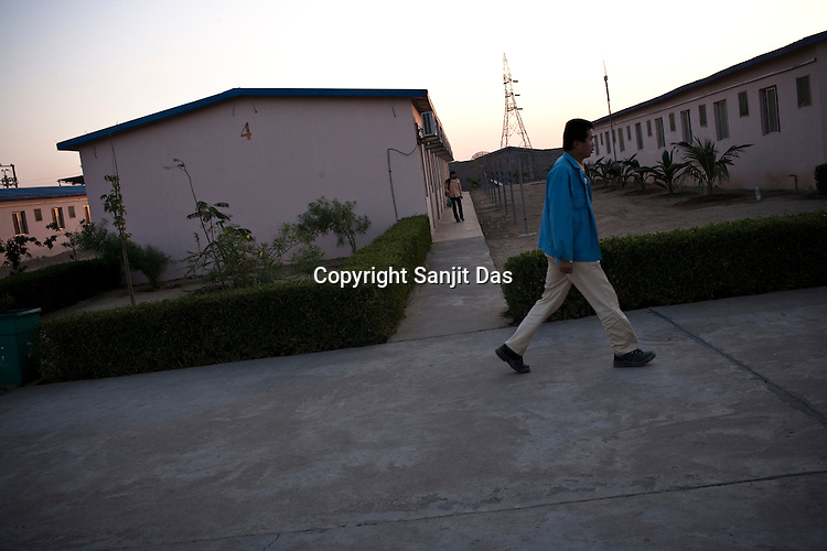 Chinese workers head for work at the Chinese Colony in the Adani Power plant in Mundra port industrial city of Gujarat, India. Indian power companies have handed out dozens of major contracts to Chinese firms since 2008. Adani Power Ltd have built elaborate Chinatowns to accommodate Chinese workers, complete with Chinese chefs, ping pong tables and Chinese television. Chinese companies now supply equipment for about 25% of the 80,000 megawatts in new capacity.