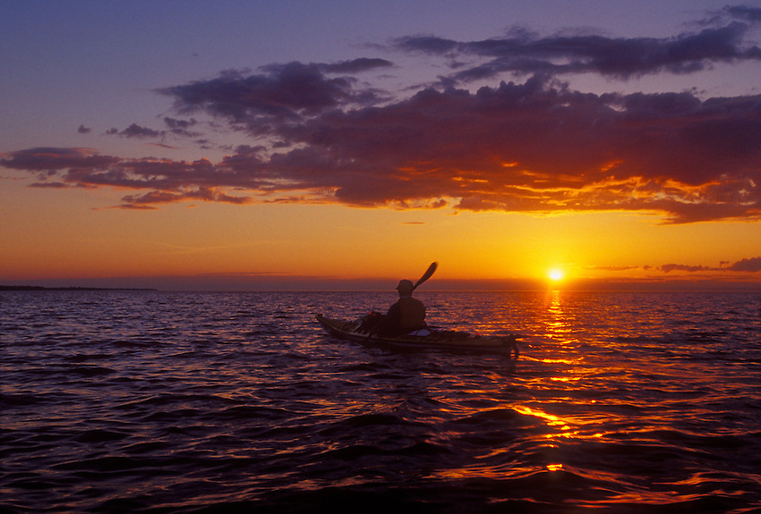 A sea kayaker is silhouetted by a setting sun as she paddles Lake Superior in Apostle Islands National Lakeshore near Bayfield, Wis.