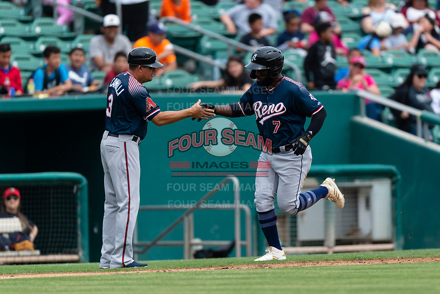 Reno Aces right fielder Abraham Almonte (7) is congratulated by hitting coach Jason Camilli (3) after hitting a home run during a game against the Fresno Grizzlies at Chukchansi Park on April 8, 2019 in Fresno, California. Fresno defeated Reno 7-6. (Zachary Lucy/Four Seam Images)