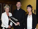 Linda Breen and Debbie Englishby make a presentation to Fr Emlyn McGinn in the Medical Missionary of Mary auditorium. Photo:Colin Bell/pressphotos.ie