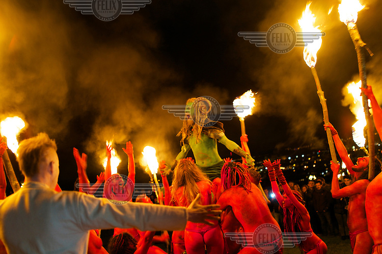 The 'Green Man' is held aloft by semi naked dancers with bodies painted in red dancing around a group of torch waving revellers at the annual Beltane Festival on Carlton Hill in Edinburgh. <br /> <br /> The Beltane Festival is an annual event when winter is purged by fire. From sunset on 30 April until early morning, over 300 volunteers create a dramatic reimagining of pagan gaelic folklore surrounded by a crowd of 6000 people. The May Queen arises to herald summer through a battle between elemental forces of order and chaos reaching a climax in the death of the green man in his winter form before bringing him back to life.