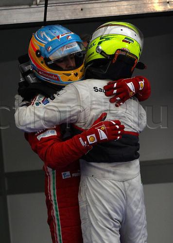 25.03.2012. Kuala Lumpur Malaysia. Formula 1 GP Malaysia in Kuala Lumpur  Fernando Alonso Scuderia Ferrari hugs second place Sergio Perez Mendoza clean F1 team at the finsh of the race