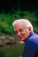 Older man, 80 years, smiles with the stories of friends and family, sitting in garden near stream, Midwest USA