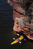 KAYAKERS IN A TANDEM KAYAK EXIT A SEA CAVE AT SQUAW POINT IN THE APOSTLE ISLANDS NATIONAL LAKESHORE NEAR BAYFIELD, WISCONSIN.