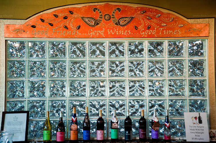 Behind the tasting bar, Narmada Winery features a block glass wall topped by artistic rendition of the winery's signature peacock, with a display of prize-winning vintages below.  (The winery's fermentation work room is on the other side of the glass wall.)