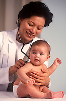 Doctor with stethoscope examines infant.