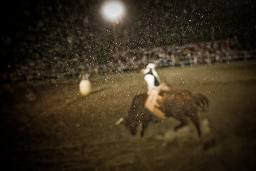 Dust and grit fills the air at the rodeo in Utopia, Texas. June 28, 2008.