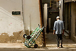 A man walks down a street near the Muscat Souq in Oman.