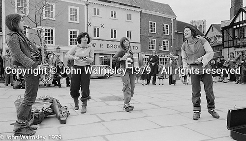 The York Street Band playing in York, March 1979.  Dena Attar on saxophone,  then the three members of the YSB: Sarha Moore (sticks), Anthea Gomez (accordian) and Ros Davies (tambourine).  Sarha Moore and Ros Davies went on to play in The Bollywood Band, and Ros also joined the Grand Union Band, in London.  Anthea Gomez went on to write and play music for the theatre and then BBC Drama before changing direction.