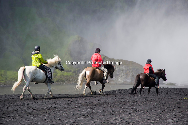 Riders on Icelandic Horses Enjoying Spray from Skogafoss Waterfall in South Iceland