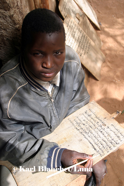 Talibe learning coranic versets written on wooden boards outside the house of the marabout in Maradi, Niger. In Niger, coranic schools still exist and are very traditional. Talibe, pupils, even go and beg for money and food in the afternoon in order to pay the marabout.