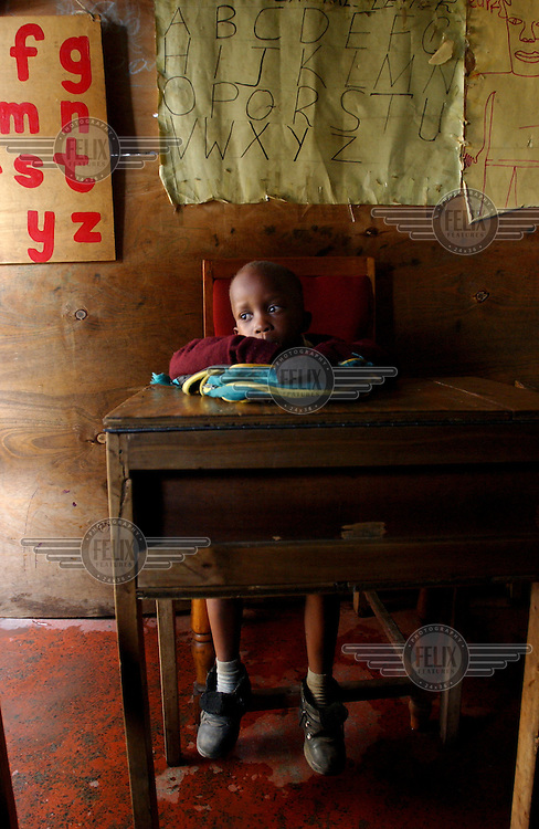 Mandela Twilimuli sits in a classroom after all the other children have left, waiting for his teacher to drop him outside his house where he will wait for his mother to finish work.