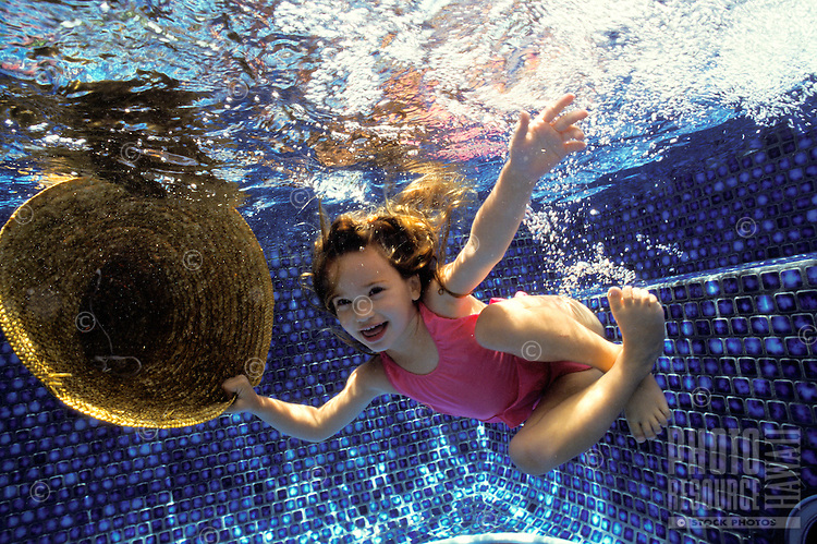 Girl playing with a straw hat and swimming under water in a pool