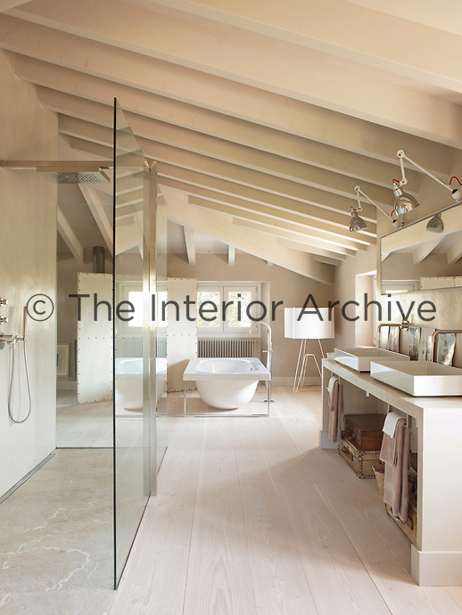 A spacious bathroom in neutral tones with a beamed ceiling and wood floor. Two washbasins are set on a unit with a mirror and wall lamps above. A shower area is separated by a glass screen and a free-standing bath is stands at one end of the room.